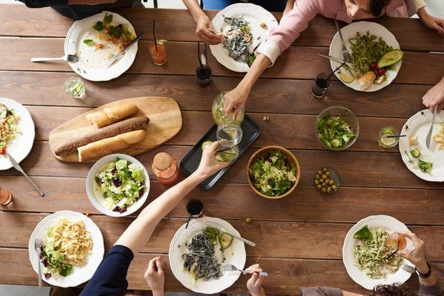 Pohled na tabuli stolu s mnoha talíři naplněnými saláty